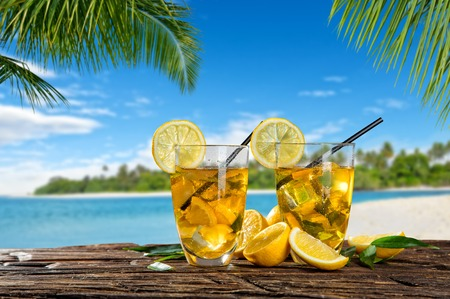 Glasses of summer ice tea drink placed on wooden planks, blur beach as background Stock Photo
