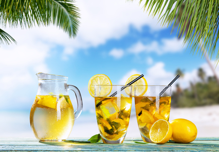 sand glass: Glasses of summer ice tea drink with tea-pot placed on wooden planks, blur beach as background Stock Photo