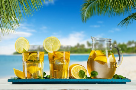 tea table: Glasses of summer ice tea drink with tea-pot placed on wooden planks, blur beach as background Stock Photo