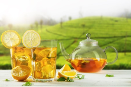 Two cups of ice tea and tea-pot served on wooden table, plantation on background