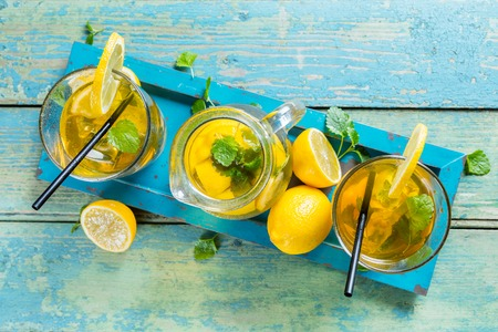 Lemon ice tea glasses and pot served on wooden table Imagens