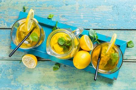 té helado: Limón vasos de té de hielo y la olla que se presentan en la mesa de madera