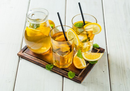Lemon ice tea glasses and pot served on wooden table Stock Photo