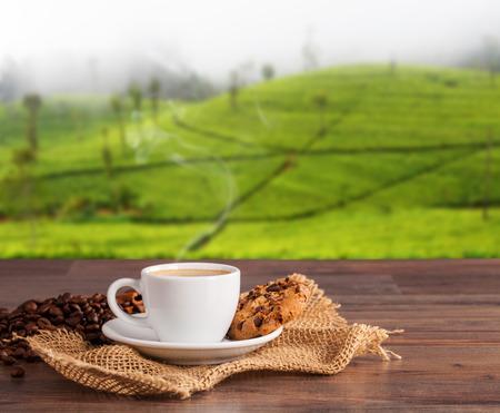 Taza de café en la mesa de madera con las plantaciones de desenfoque de fondo