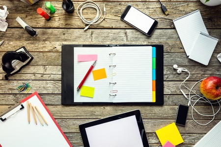 tecnología informatica: Libreta en blanco en la mesa de oficina con un montón de cosas. Puede ser utilizado como copyspace para el texto. Concepto del interior de la oficina moderna inconformista. Opinión de alto ángel