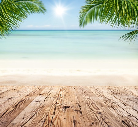 product: Empty wooden planks with blur beach on background, can be used for product placement, Palm leaves on foreground