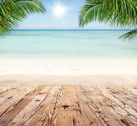 Leere hölzerne Planken mit Unschärfe Strand auf Hintergrund, kann für die Produktplatzierung verwendet werden, Palmblätter auf den Vordergrund