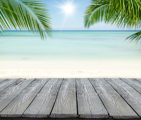 Empty wooden planks with blur beach on background, can be used for product placement, Palm leaves on foreground 版權商用圖片 - 55296506