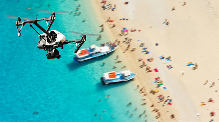 drone: Drone for industrial works flying above beach. Concept of pottential danger of aircraft collision