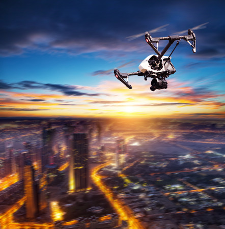 Drone silhouette flying above modern city panorama at night Фото со стока