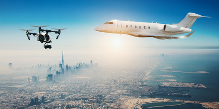 potentially: Drone potentially being hit by commercial airplane above modern city panorama. Concept of aircraft accident. Thread of collision