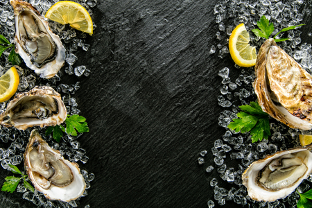 Oysters served on stone plate with ice drift and lemon.