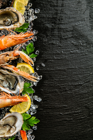Seafood served on black stone, placed on ice drift