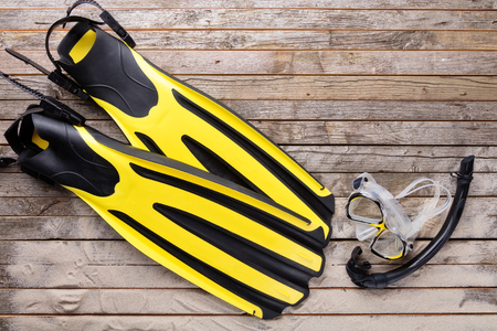 fins: Mask, fins and snorkel on wooden desk. Equipment for diving Stock Photo