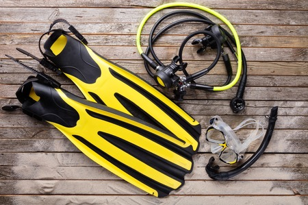 regulator: Mask, fins, regulator and snorkel on wooden desk. Equipment for diving