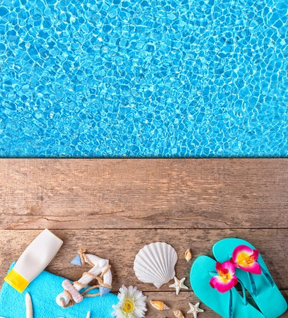 aerial animal: Beach accessories on wooden background placed over swimming pool. Copyspace for text