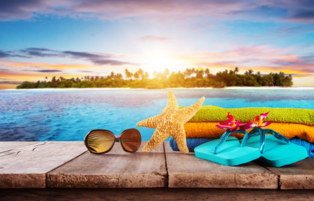 Beach accessories for travelling placed on wooden planks. Tropical beach on background