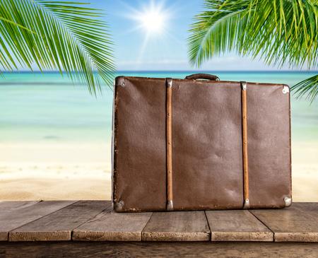 maleta: maleta de viaje en tablones de madera vieja, playa tropical en el fondo