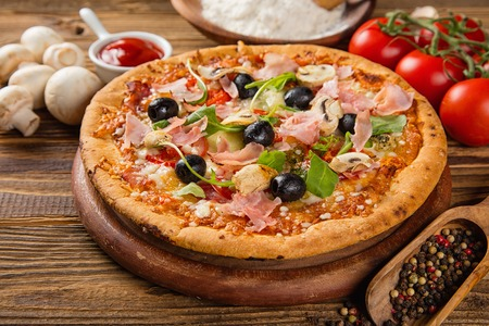Rustic pizza with mozzarella, olives, basil and ham. Served on vintage wooden table