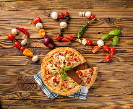fastfood: Rustic pizza with pizza text above made of fresh ingredients. Served on vintage wooden table