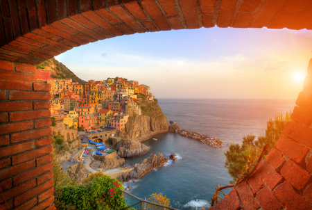 view on sea: Old village Manarola shot from brick frame window, Cinque Terre coast, Italy. Beautiful sunset view in high dynamic range. Stock Photo