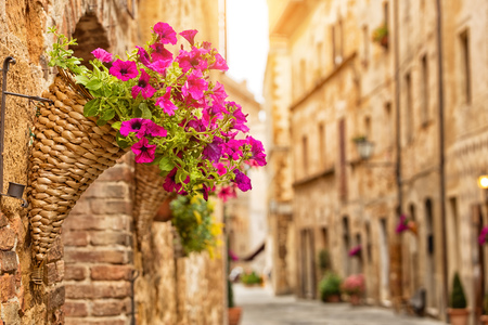 pienza: Colorful street in Pienza with detail of flowers, Tuscany, Italy Stock Photo
