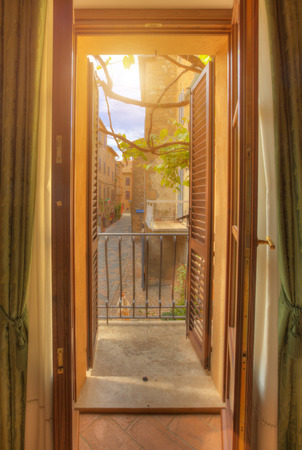 Window view  of colorful street in Pienza with many decoration flowers and trees, Tuscany, Italy