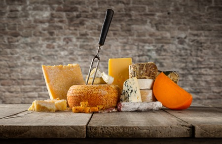 emmental: Various types of cheese placed on wooden table, copyspace for text. brick wall on background