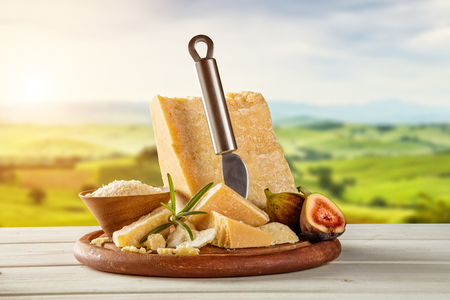 Parmezaanse kaas op de snijplank geplaatst op hout, vervagen landschap op de achtergrond