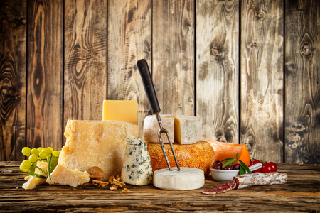 food still: Various types of cheese placed on wooden table, copyspace for text. Wooden planks on background Stock Photo