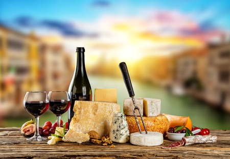 types of glasses: Various types of cheese, glasses and bottle of red wine placed on wooden table, copyspace for text. Blur old town on background Stock Photo