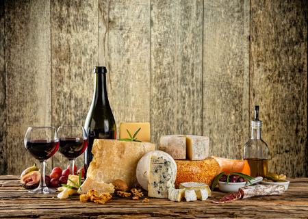 Various types of cheese, glasses and bottle of red wine placed on wooden table, copyspace for text. Wooden planks on background