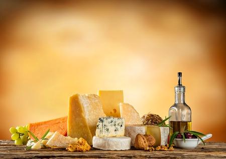 様々 なタイプのチーズは、木製のテーブル、抽象的な背景付きのテキスト copyspace 上に配置