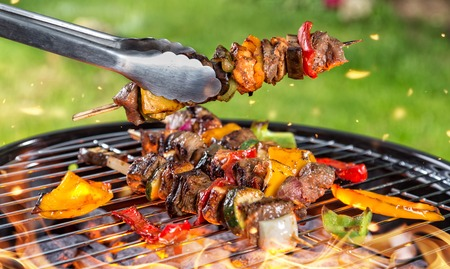 shishkabab: Full grill and meat skewer being hold in sticks