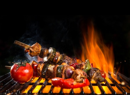 shishkabab: Meal skewer on grill with fire, isolated on black background