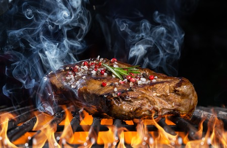 Beef steak on grill in fire with black background