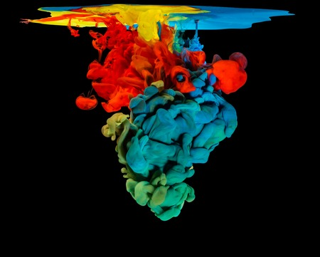 black ink: Mix of colored ink in water creating abstract shape, isolated on black background