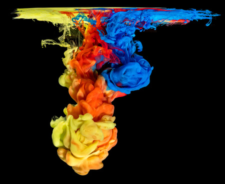 Mix of colored ink in water creating abstract shape, isolated on black background
