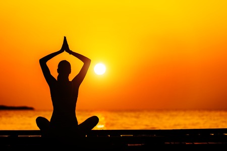 copyspace: Silhouette of young woman practicing yoga in beautiful sunrise Stock Photo