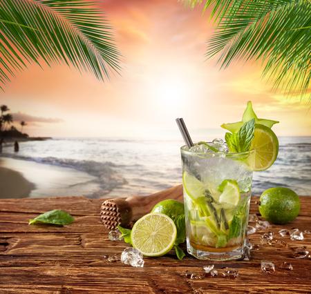 cocteles de frutas: Coctel del verano con la playa de la falta de definición en el fondo Foto de archivo