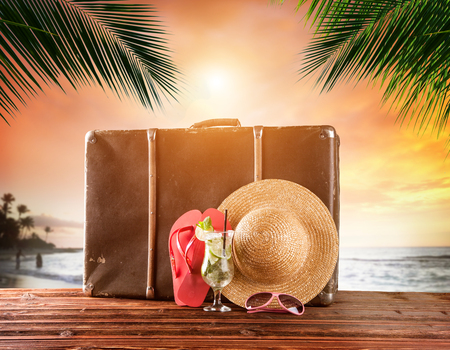 Old suitcase on tropical beach in beautiful sunset, travel concept