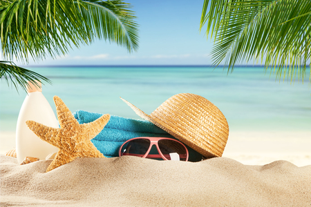 Summer accessories on sandy beach, blur sea on background. Summer exotic relaxation concept Archivio Fotografico