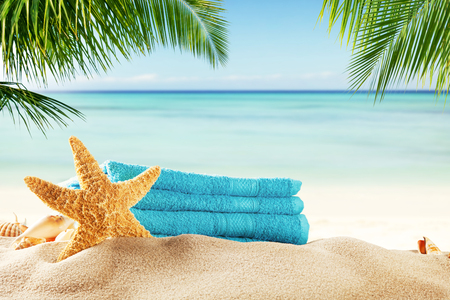 Summer accessories on sandy beach, blur sea on background. Summer exotic relaxation concept