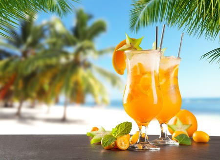 summer fruits: Summer cocktails with blur beach on background