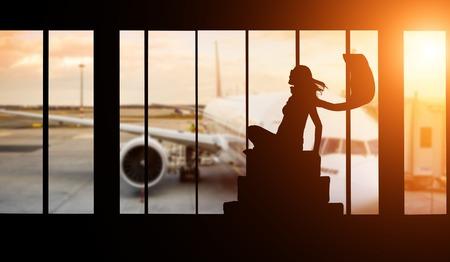Jonge vrouw silhouet op de luchthaven met koffer. Big passagiersvliegtuig op de achtergrond. Reisconcept van het luchtvervoer