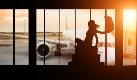 voyage avion: Young woman silhouette at Airport with suitcase. Big passengers plane on background. Travel concept of air transportation
