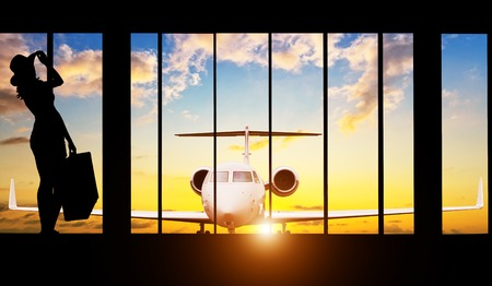 jet plane: Young woman silhouette at Airport with suitcase. Private jet plane on background. Travel concept of air transportation Stock Photo
