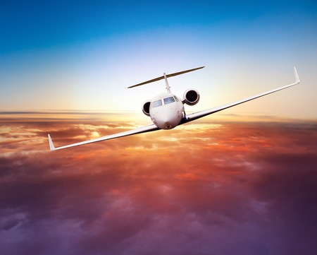 Private jet plane flying above clouds in beautiful sunset. Shot from front view Standard-Bild
