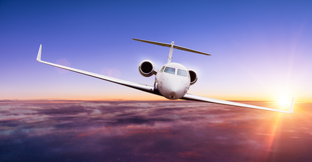 Private jet plane flying above clouds in beautiful sunset. Shot from front view Stock Photo