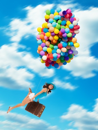 flying woman: Young woman holding balloons and old suitcase, flying above clouds. Concept of travel and freedom